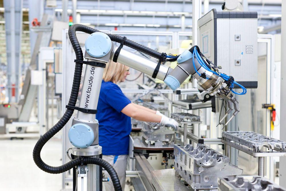 Robot og menneske samarbeider om å sette inn glødeplugger i bilmotorer hos Volkswagen.
