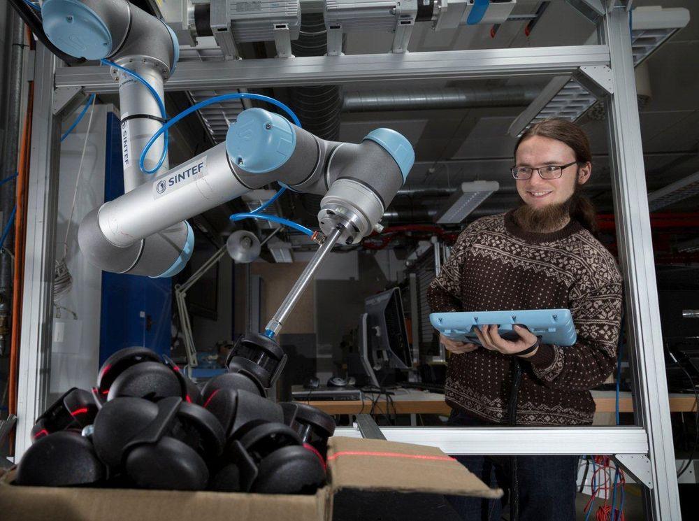 SINTEF-forsker Sigurd Albrektsen følger med når roboten plukker stolhjul fra en kasse. De optiske sensorene som styrer robotarmen er montert i en annen robot.