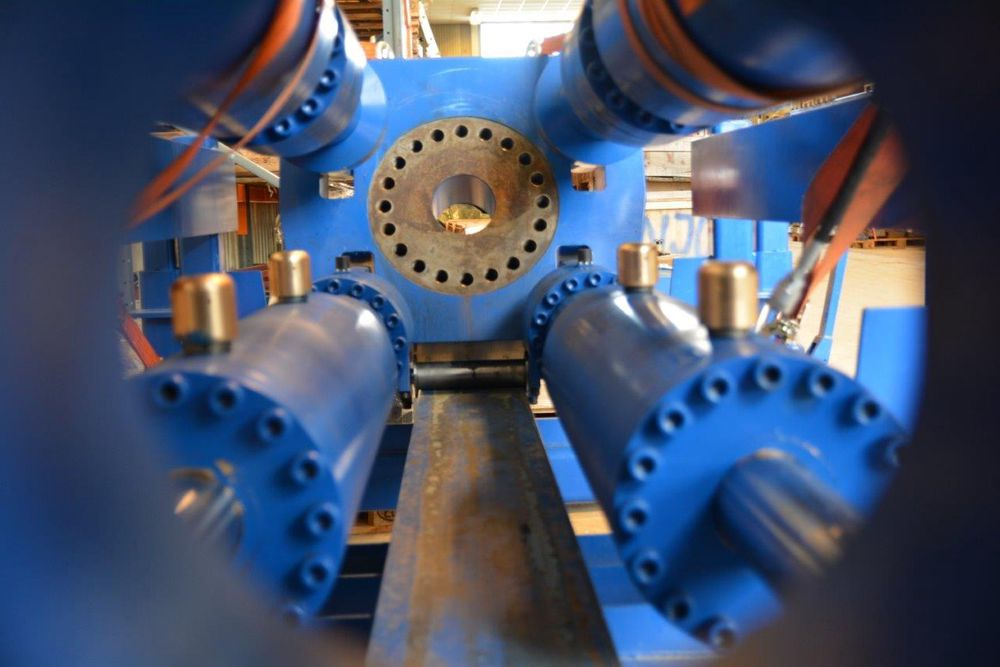 Nærbilde av rørbøyemaskinen, med feste for rørflens i midten og fire kraftige hydraulikksylindre som bøyer rørene.
