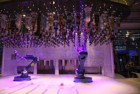 To Kuka-roboter serverer drinker. Men det går seint.