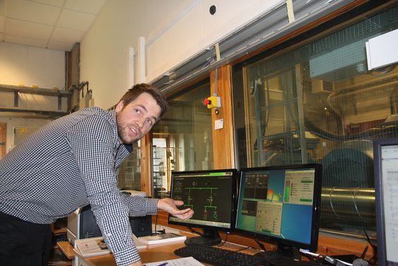 Forskningsingeniør Mikael Ånestad i ABB styrer generatorsett og hybridteknologien fra kontrollrommet med vindu ut mot laboratoriet.