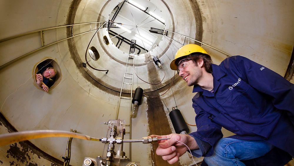Forsker Jørgen Skancke i bunnen av tårnbassenget. Dysen brukes til å simulere ukontrollerte olje-utslipp – men da er altså den seks meter høye tanken fylt med vann. Ingeniør Frode Leirvik følger med fra et av bassengets vinduer.