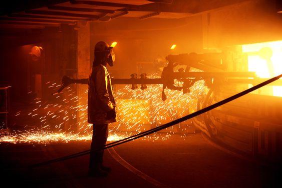 Arbeidere i flammehemmende drakter renser tappekanalene på den ombygde og miljøvennlige smelteovnen på Elkem Salten.
