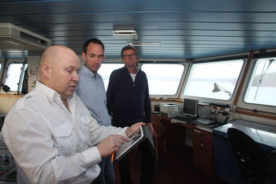 Kaptein Torleif Bakken på Bastø II med Rex ruteplanlegger på en iPad. Kaptein og sikkerhetsrådgiver Gisle Stava i Bastø Fosen har bidratt  til utviklingen av Rex som Geir Fagerhus (bakerst) i Marsec-XL står for.