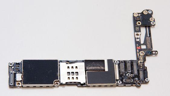 Hovedkortet sett forfra. SIM-kortholderen sees i midten. Apples A8-prosessor sitter til høyre for denne. De fleste komponentene er beskyttet av metalldeksler som er loddet fast i kretskortet.