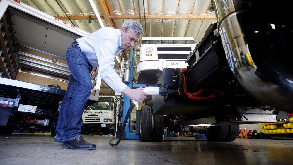 Ian Wright drar ut pluggen fra en av lastebilene selskapet har installert den elektriske drivlinjen sin på.