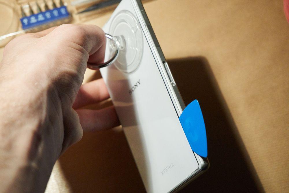 Med en gang vi fikk en liten glippe på baksiden, dyttet vi iFixits lille, blå plekter inn i åpningen for å holde den der.