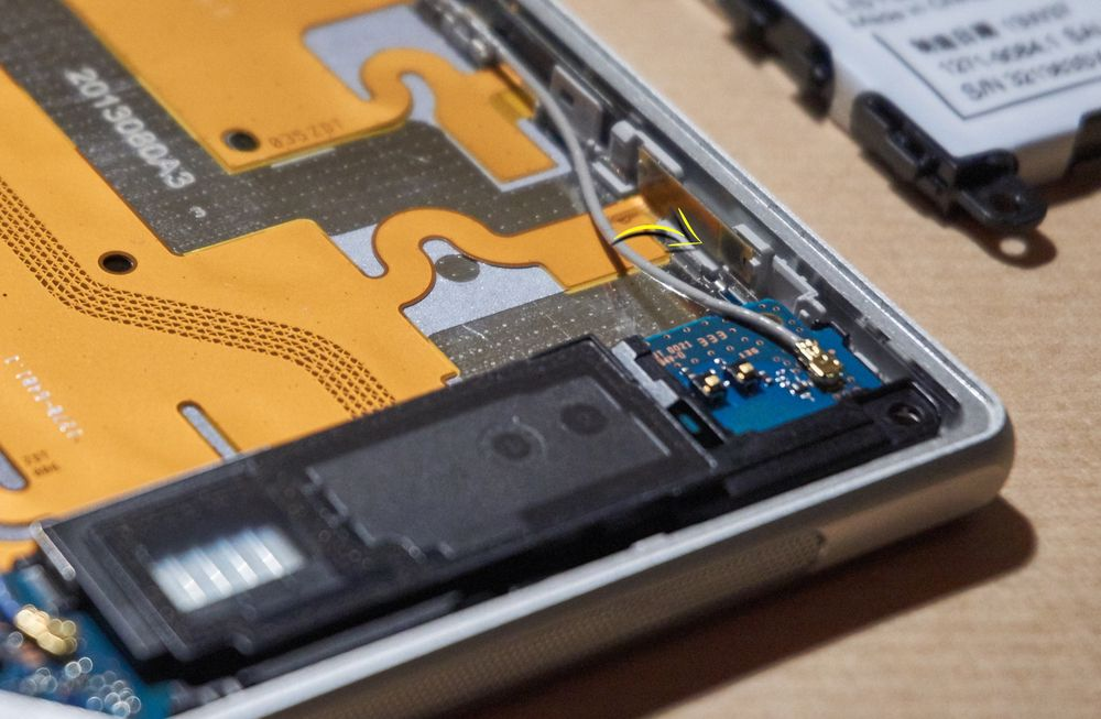 Med alle tilkoblingene klikket på plass, kunne den svarte plastdelen plasseres trygt tilbake. Det var imidlertid viktig å legge disse ledningene nøyaktig slik de var da vi åpnet telefonen. I dette tilfellet kunne ledningen ha kommet i klem da vi satte i batteriet – og vi ville mistet enten WiFi- eller telefonsignalet vårt.