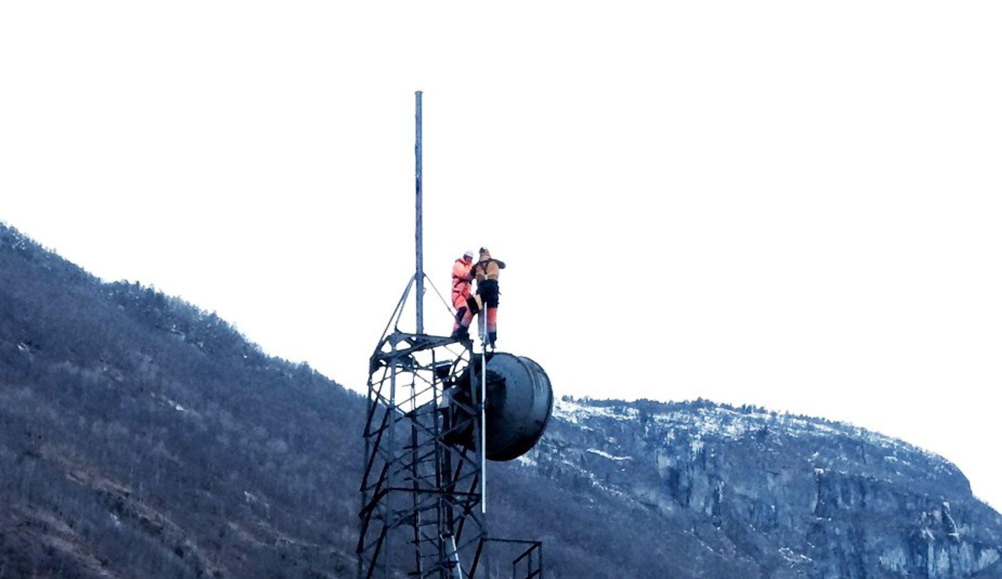 Mannskap fra Eltel strekker kabler fra Telenors mobile container og opp i mobilmasten som overlevde storbrannen i Lærdalsøyri.