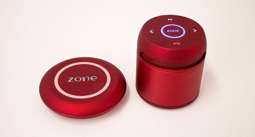 """Zone: Den lille høyttaleren kjennes solid ut, men det er den vel også siden den er laget i aluminium. Da vi fotograferte ringte telefonen og vi tok den via den høyttalende funksjonen. Derfor lyser den røde """"legg på""""-knappen.  Ladeplaten til venstre lad"""