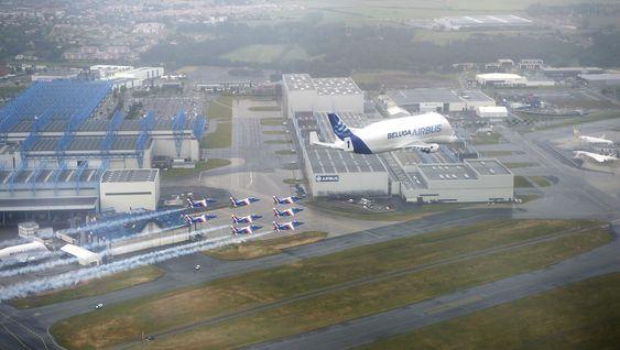 Beluga og Patrouille de France i formasjon over Airbus-fabrikken ved Toulouse-Blagnac lufthavn.