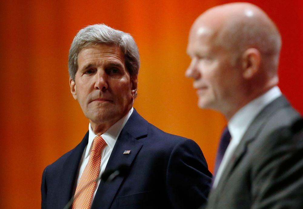 USAs utenriksminister John Kerry (t.v.), her sammen med sin britiske kollega William Hague, sier USA vurderer å gjenoppta forbindelsen med erkefiende Iran for å finne ut av hvordan man kan få løst krisen i Irak.