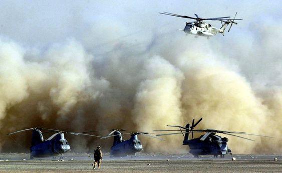 En CH-53E Super Stallion går inn for landing i Afghanistan. På rullebanen står en annen CH-53E og to CH-46E Sea Knights.