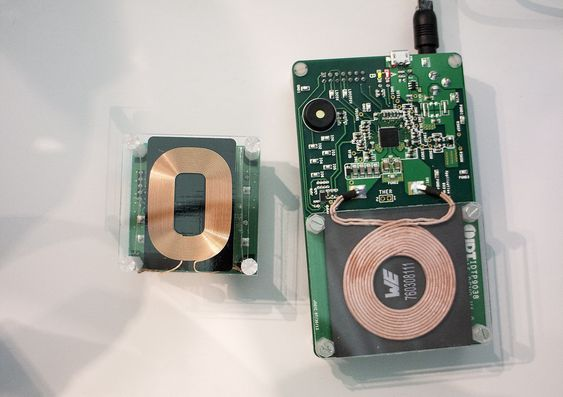 Induktans avkledd: Trådløs lading av produkter som følger Qi-standarden bruker to spoler. En i ladeplaten. En telefon, med mottakerspole i baklokket plassers oppå ladeplaten slik at spolene ligger inntil hverandre.