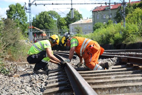 Micael Anderson og Harald Olsen fra Norsk Jernbanedrift legger skinner på Østfoldbanen etter at sporene ble revet i forbindelse med bygging av en ny bru over den kommende byggegropa til Follobanen.