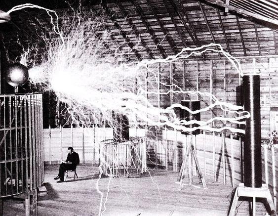 Bilde av en assistent i laboratoriet i Colorado Springs. Bildet viser Teslas «forsterkende sender» (en variant av Teslaspolen) som genererer millioner av volt. Lysbuen er nesten syv meter lang. Teslas egne notater identifiserer bildet som en multieksponering. (Kilde: Wikipedia)