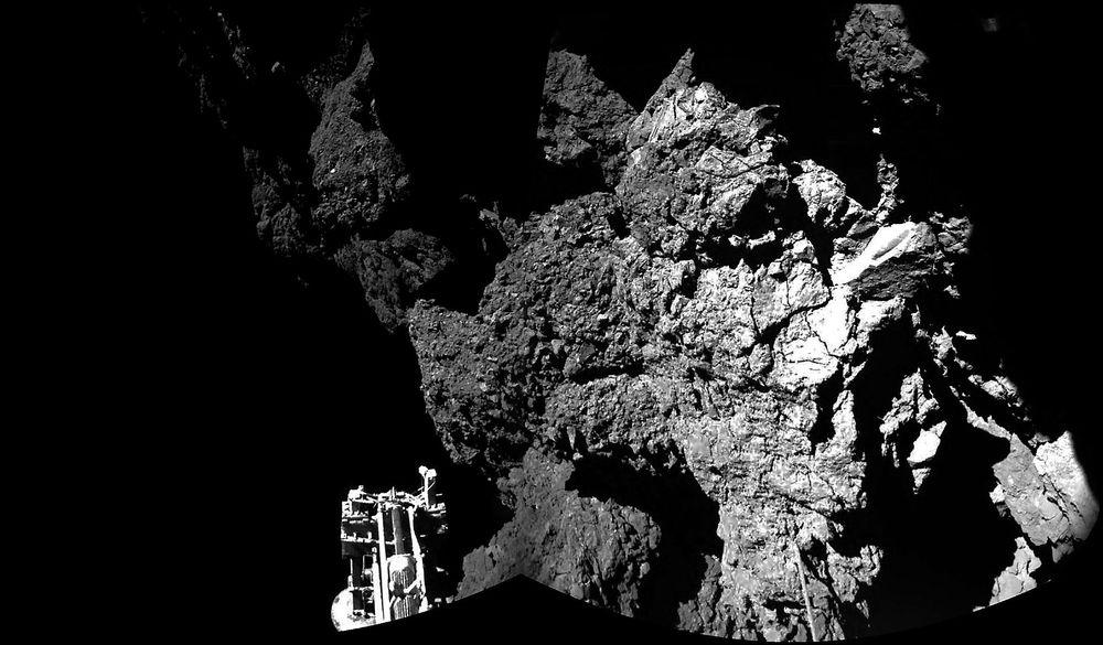 Her er Philae mens den står på bakken av kometen. Den ene foten til landeren kan skimtes nede til venstre.