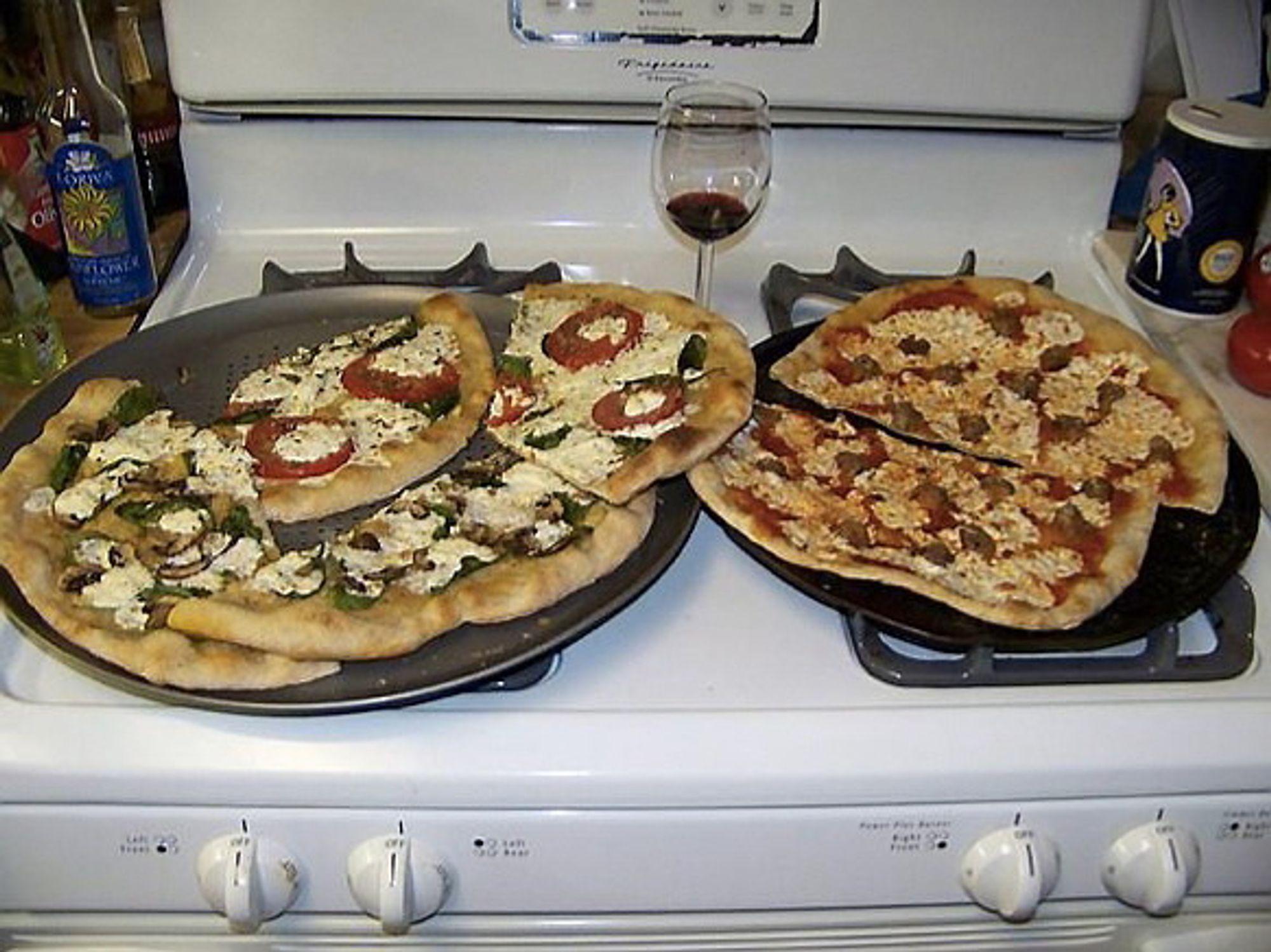 Slik forklarer Googles nettverk dette bildet: Two pizzas sitting on top of a stove top oven.