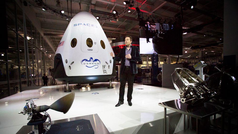 SpaceX-sjef Elon Musk, som også er sjef i Tesla, poserer foran den nye romkapselen som etter planen skal ta med seg mennesker ut i verdensrommet og tilbake igjen allerede i 2017.