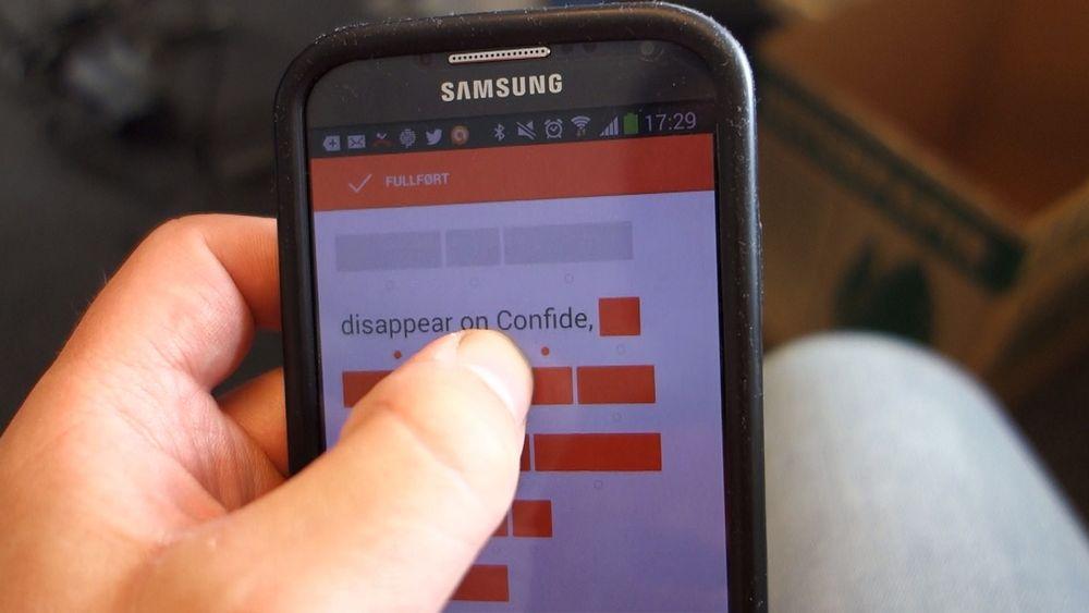 Testmelding som demonstrerer hvordan Confide fordekker deler av beskjeden og synliggjør delene der fingeren peker.