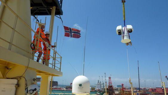 Installasjon: En Aptomar-sensor heises om bord for installasjon på et skip. Selskapet har utviklet avanserte sensorer som kan måle tykkelsen på oljeflak og observere objekter i sjøen i mørke og i dårlig sikt.