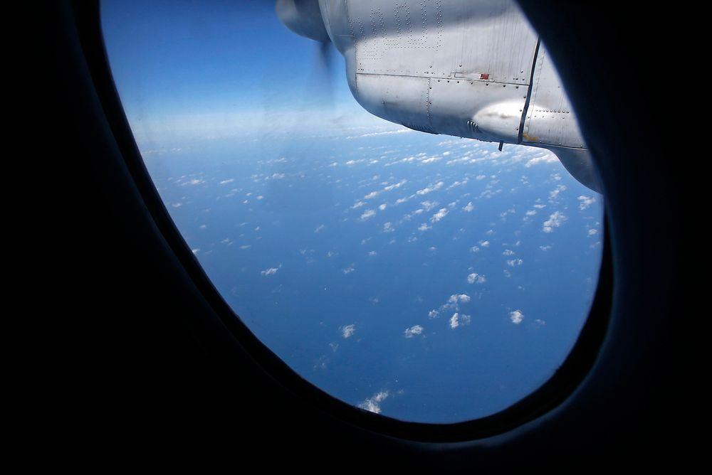 Her leter et AN-26-fly fra det vietnamesiske forsvaret etter det savnede Boeing-flyet fra Malaysia Airlines. FOTO: REUTERS