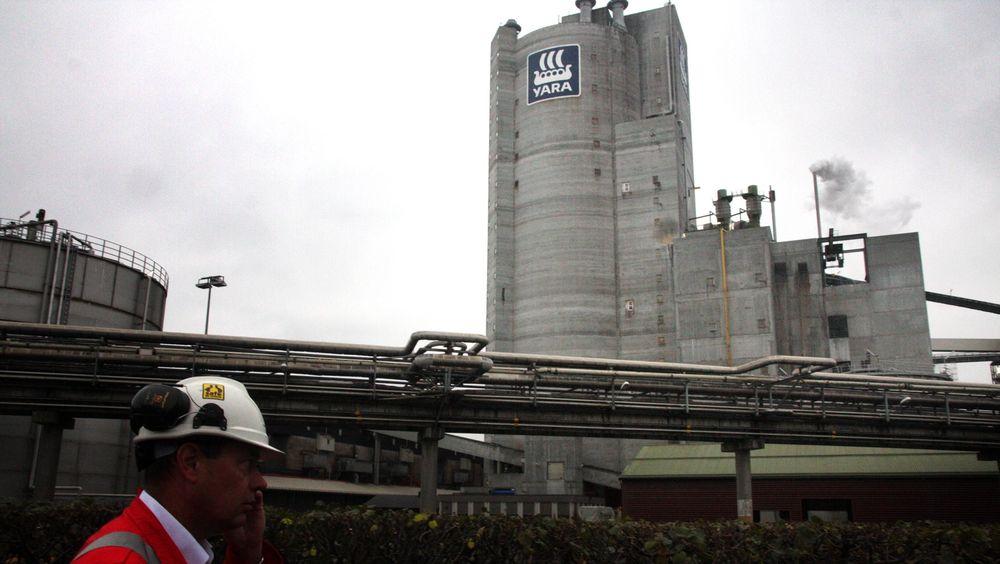 Logo: Yaras store logo på det 109 meter høye tårnet på fabrikk 4. Fabrikksjef Per Knudsen haster forbi.