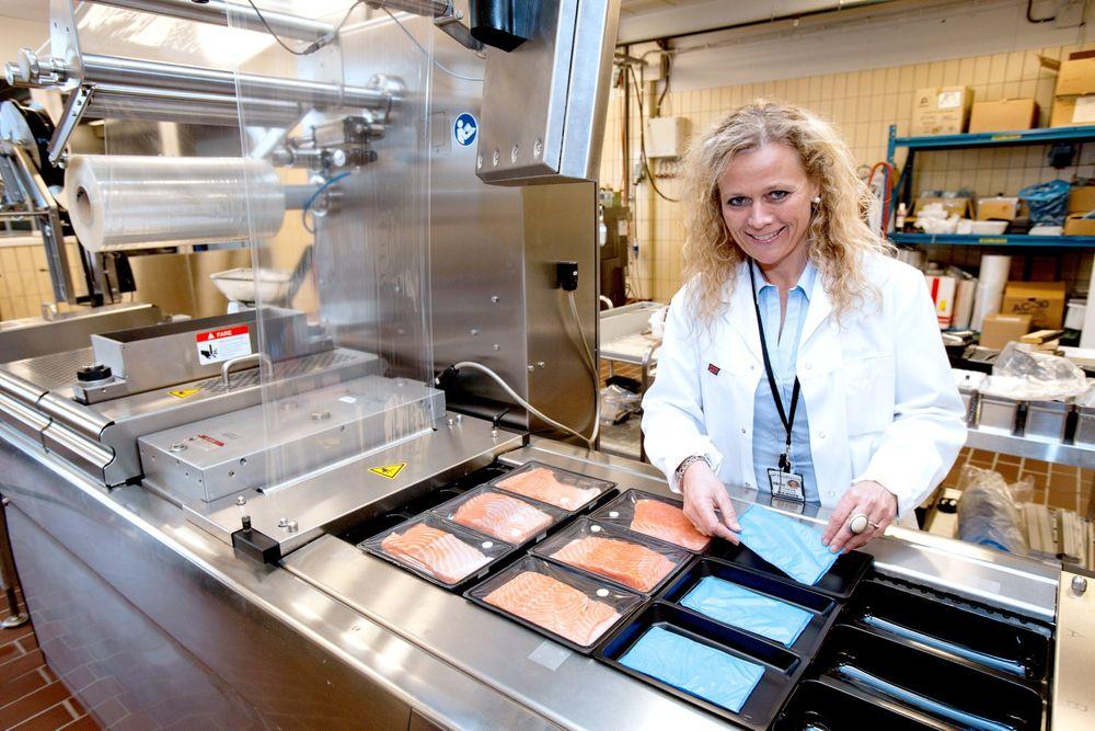 Nytt system: Seniorforsker Marit Kvalvåg Pettersen ved Nofima viser hvordan fiskestykkene legges opp på emitterputen som gir fra seg konserverende gass.  Foto: Nofima