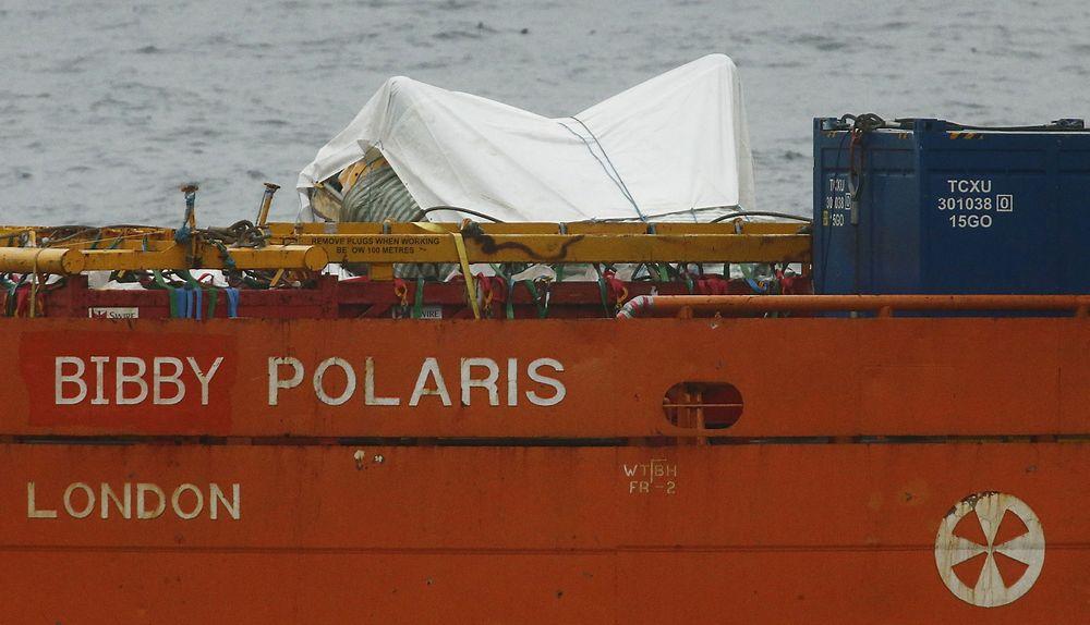 Tildekkede vrakdeler fra AS332L2-maskinen som havarerte utenfor Shetland fredag kveld, i ferd med å fraktes til land mandag formiddag.
