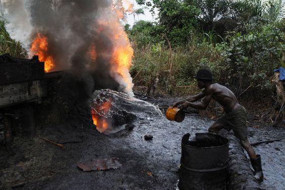 En nigerianer kaster vann på ilden for å redusere heten ved et primitivt og ulovlig oljeraffineri i delstaten Bayelsa sør i Nigeria. Tusenvis av nigerianere driver med det de kaller «bunkring», der de stjeler råolje fra rørledninger og raffinerer den eller selger den til kriminelle i utlandet.
