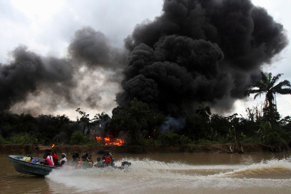 Røyk stiger til værs fra et ulovlig oljeraffineri etter at det ble ødelagt av militæret i en aksjon i delstaten Bayelsa i det sørlige Nigeria. I disse delene av landet er det vanlig at folk stjeler råolje fra rørledninger for å produsere sin egen bensin eller dieselolje. Mange mener de har mer rett til oljen enn den nigerianske staten.