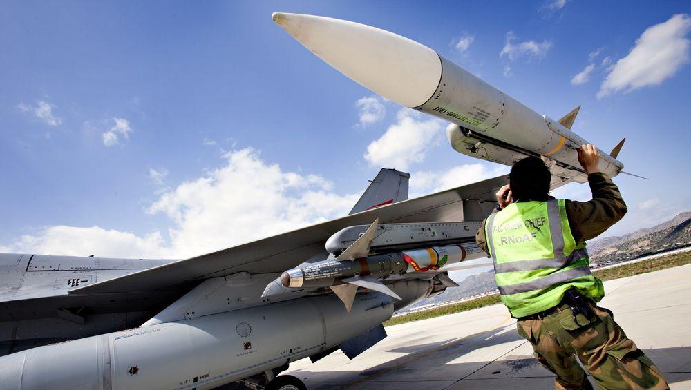 En militær tekniker kontrollerer et AIM-120B Amraam-missil på vingespissen på et norsk F-16 på flybasen Souda på Kreta i forbindelse med operasjon Odyssey Dawn for snart to år siden. Lenger inn på vingen et AIM-9 Sidewinder kortholdsmissil som Nammo også lager motoren til.  Foto: Lars Magne Hovtun/Forsvarets mediesenter