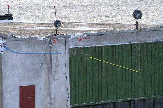 Treffpunktet oppe på det sydlige (venstre) hjørnet av hangaren. Grønn pil indikerer retningen helikopteret kom, og røde piler viser blå fargeavsetning på betongen. Ettersammenstøtet fortsatte helikopteret til venstre som antydet med blå pil.