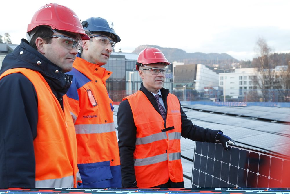 Kommunal- og moderniseringsminister Jan Tore Sanner legger ned det siste panelet på Kjørbo sammen med Ståle Rød i Skanska og Marius Holm i Zero (til venstre).