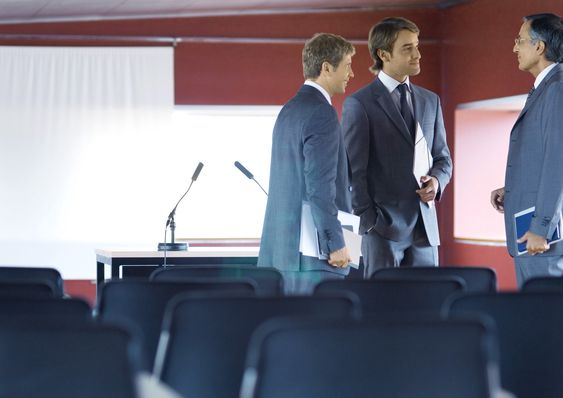 Three businessman standing, talking in conference room