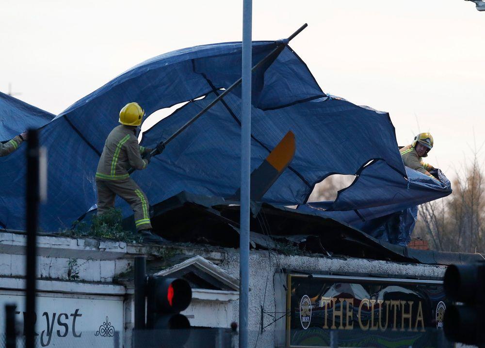 Redningsarbeidere dekker over vraket av politihelikopteret som kræsjet på taket til Clutha Vaults pub i Glascow.