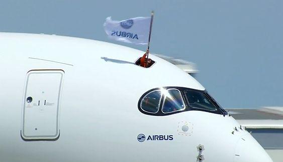 Opp fra takluka over cockpit stakk sjefingeniør Pascal Verneau opp et Airbus-flagg etter en vellykket jomfruferd med A350 XWB.