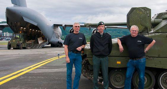 Harald Hend (f.v) i Ritek, major Albert Albertsen fra Kampvognprosjektet og Håkon Røvik i Ritek ved den første CV-90-en som leveres inn til moderniseringsprogrammet. Panservognen ble fraktet til Værnes sist lørdag i et C-17 transportfly.