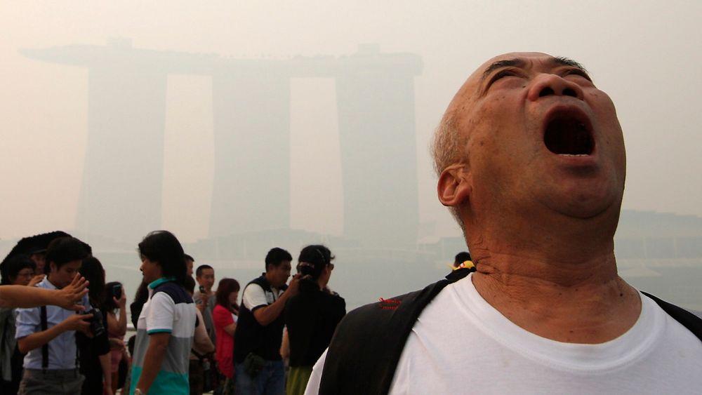 En turist gisper etter luft i Singapore, der smog – forurenset tåke – fra brenning av regnskog i nabolandet Indonesia har ført til forurensning på helsefarlig nivå.