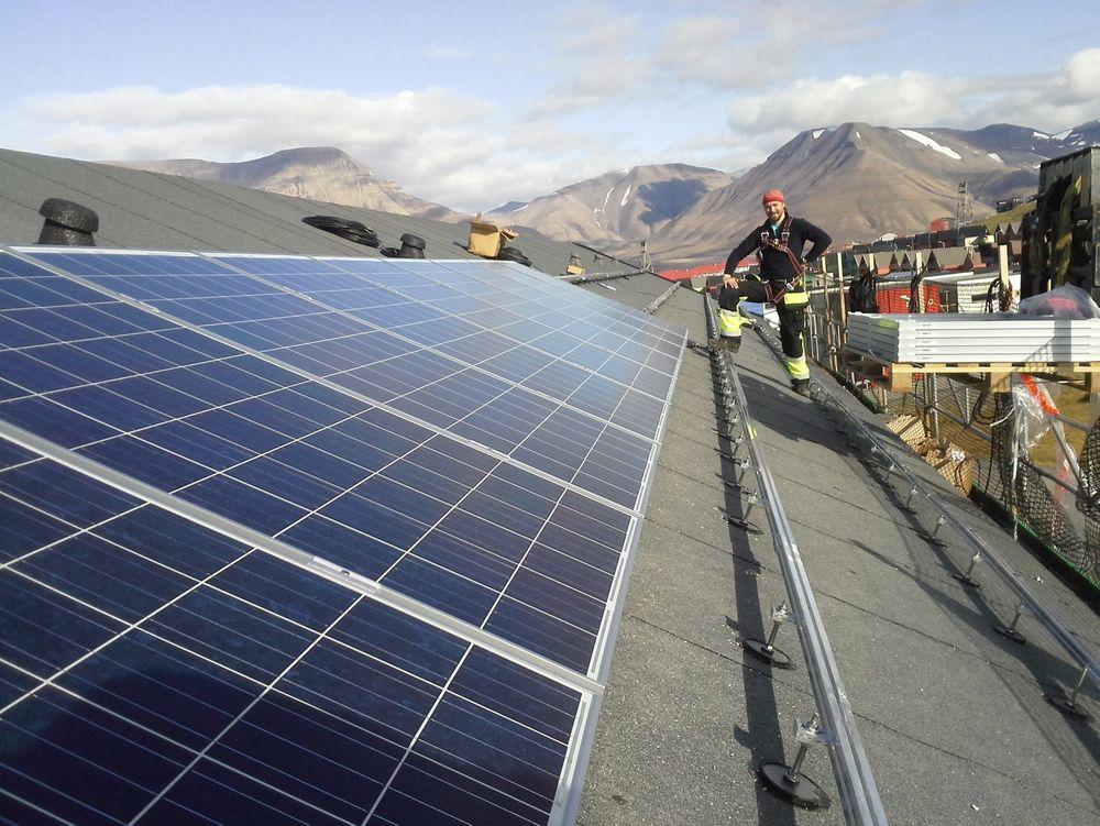 Solbes har installert solcellepaneler på bolighus i Longyearbyen. I neste omgang håper man å dekke store deler av kraftbehovet til kullgruvedriften i Sveagruva. Her med montør Christian Kjelsberg.