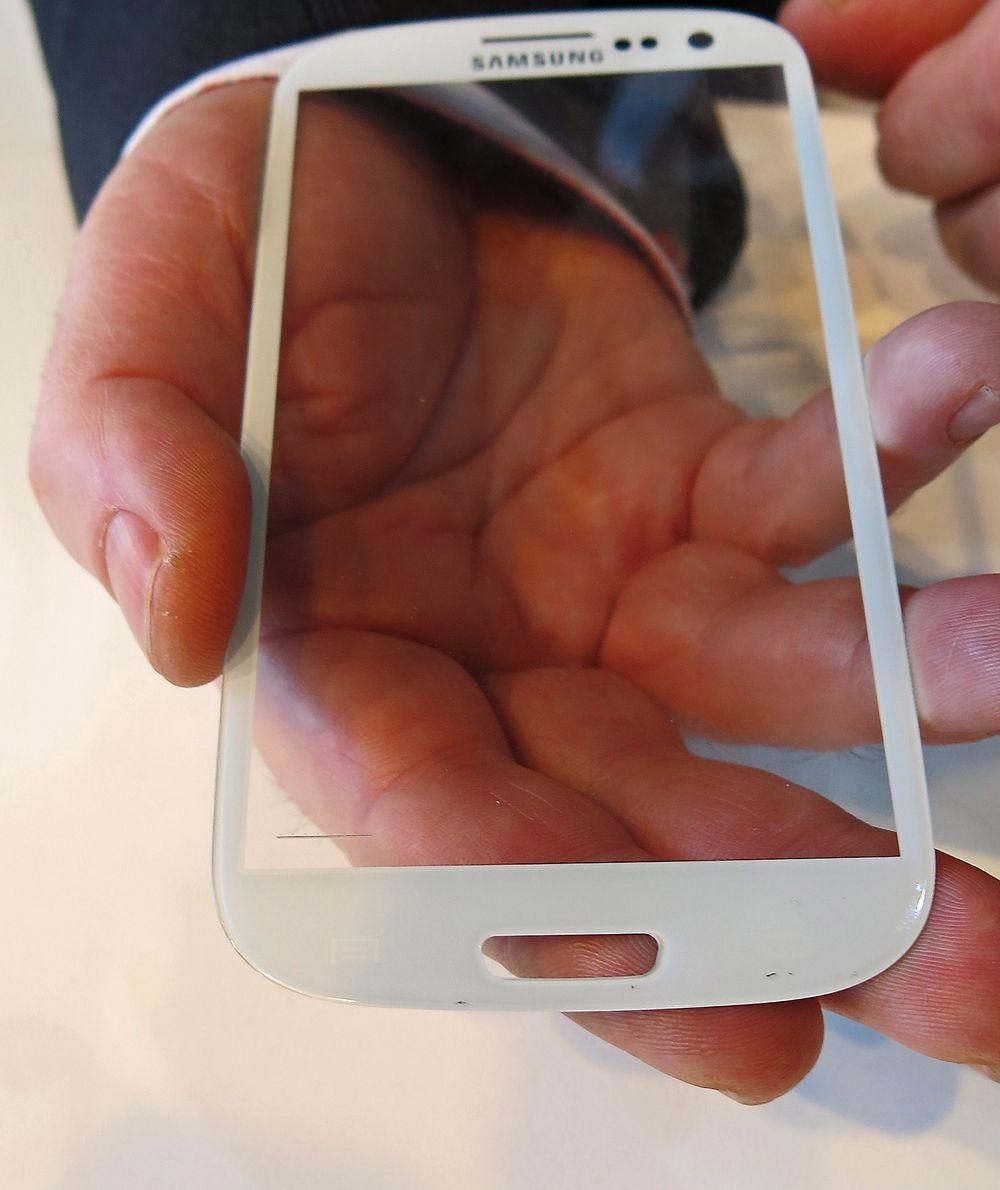 Ørsmå hull: Gjennom 132 ørsmå hull i nederste venstre hjørne på skjermen kan Idex lese fingeravtrykk. Hullene kan fylles med et ledende stoff med samme optiske egenskaper som glasset slik at de blir usynlige.