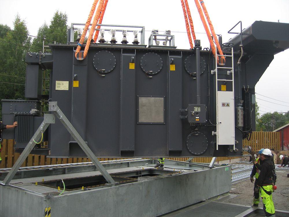 I lufta: Her løftes trefase-transformatoren på plass oppå en transportabel oljegruve. Gruven skal sikre oppsamling av olje ved transformatorfeil.