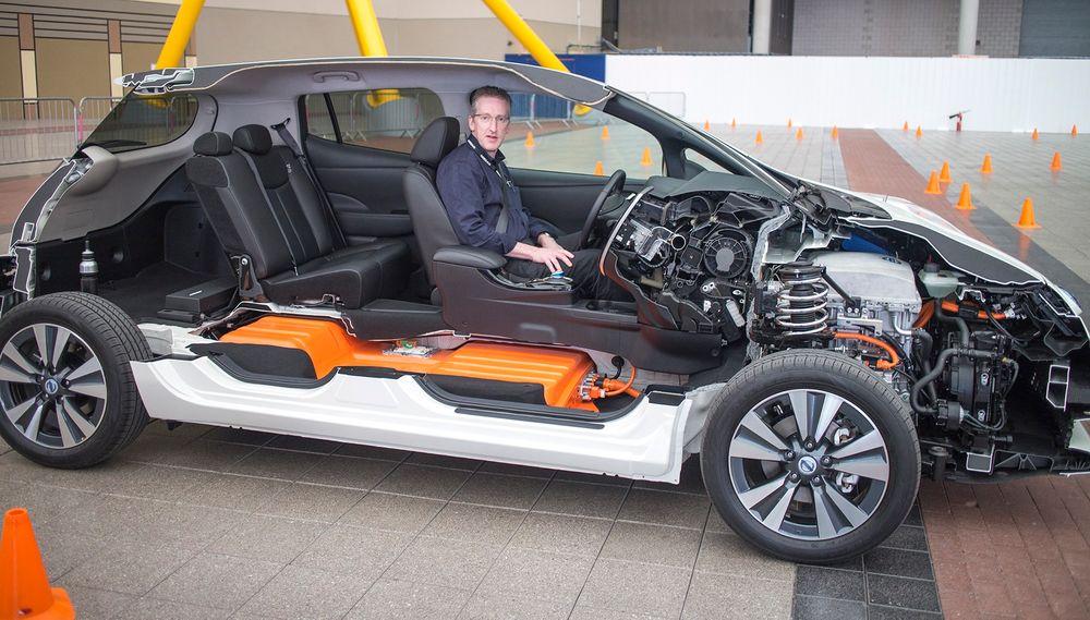 Half-Leaf: Nissan har kuttet bort nesten halvparten av nye Leaf for å vise frem de elektriske godsakene. Det oransje batteriet på 27 kWh er tungt, så det er plassert midt under bilen. Det gir Leaf svært gode kjøreegenskaper. De aller fleste biler med forbrenningsmotor har den tunge motoren foran og det påvirker dreiemomentet til kjøretøyet når man svinger.  Senioringeniør for elbiler i Nissan Europa, Tom McCabe kjører villig en runde for å demonstrere.