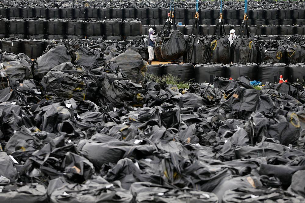 Opprydningsarbeidere flytter radioaktivt avfall ved et lager i byen Nahara ikke langt fra det katastroferammede atomkraftverket Fukushima Daiichi øst i Japan.