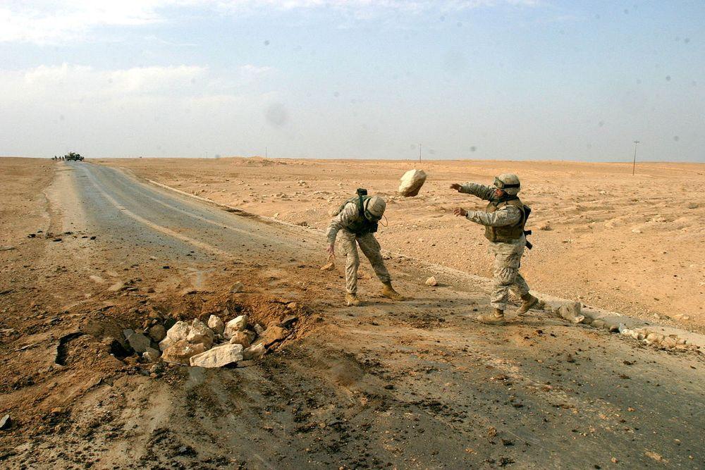 Soldater fra USAs marinekorps rydder opp etter en landmineeksplosjon på en vei i Al Qaim i Irak.