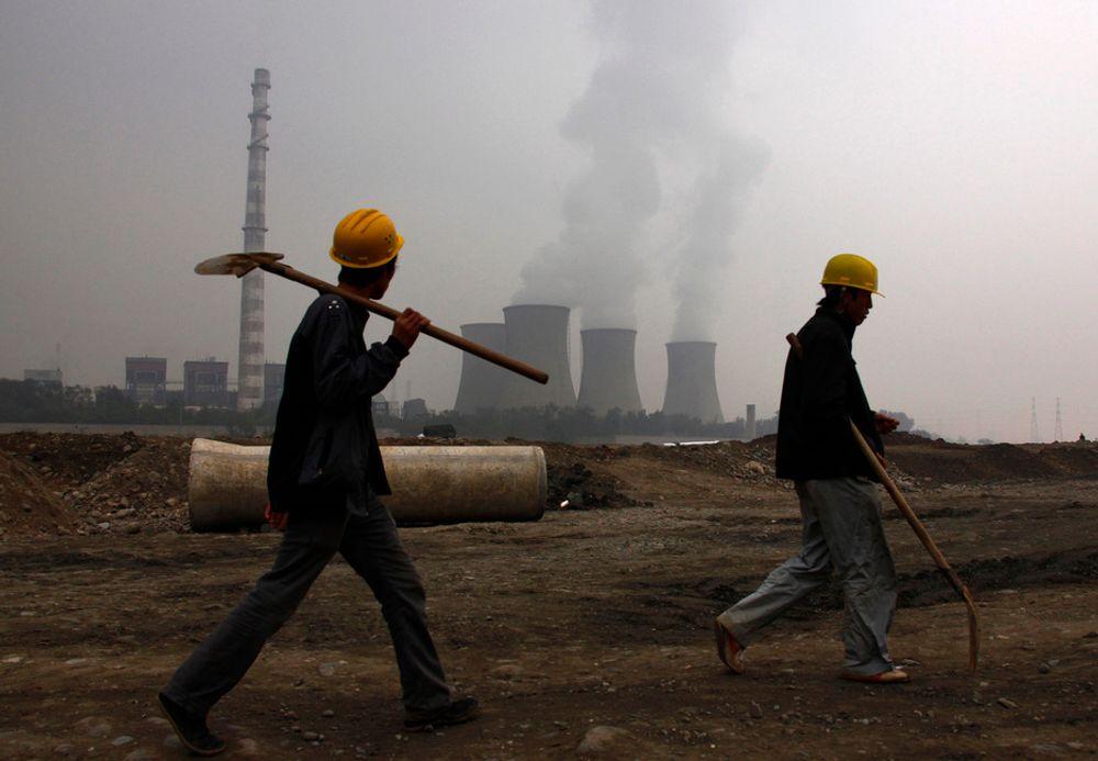 KULL: To arbeidere foran et kullkraftverk utenfor den kinesiske hovedstaden Beijing. Kullkraft er en av de viktigste kildene til utslipp av klimagassen CO2.