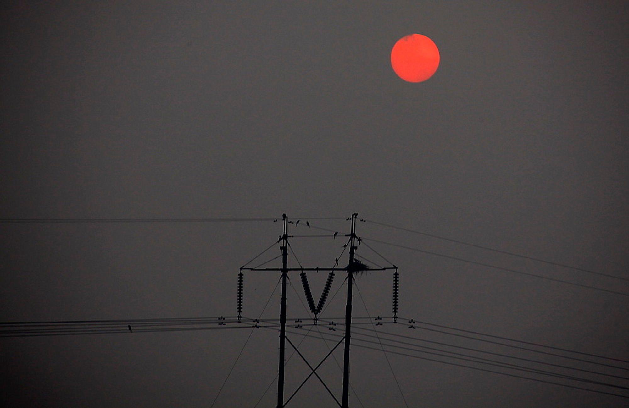SLIPPER UT MER: Sola står opp og skinner gjennom tykk smog over Beijing. En ny rapport viser at Kinas utslipp av karbondioksid er på linje med utslippene fra EU. Kinas utslipp fortsetter å vokse og økte med 9 prosent i 2011.