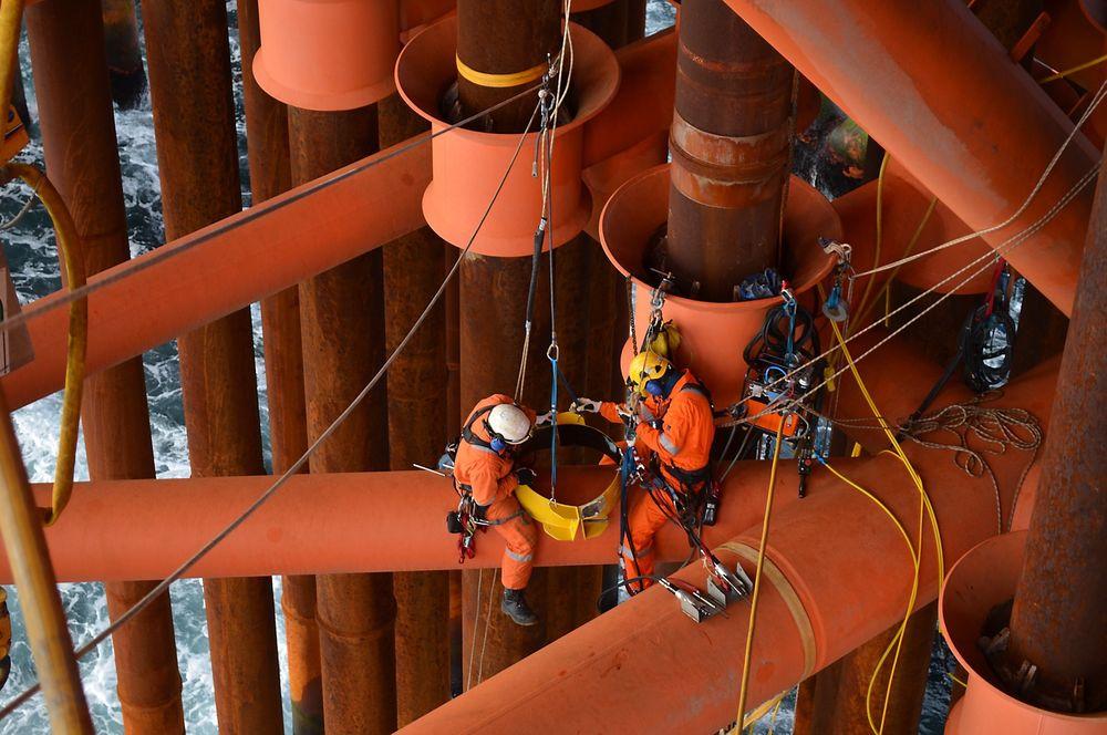 På speiderdekket sitter tilkomstteknikerne fra Can AS i fullt klatreutstyr. Arbeidsprosessen i skvalpesonen overvåkes ved hjelp av et undervannskamera og en skjerm.