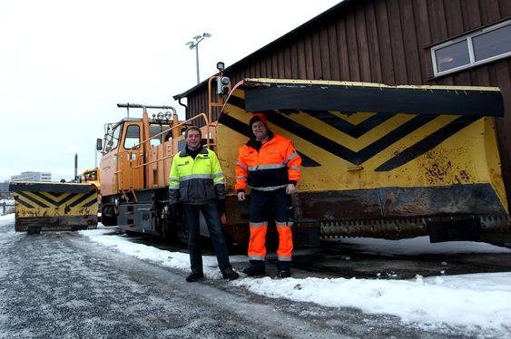 """Snøsjef Ove Fuglehaug og Knut Erik Vingebakken foran """"Stampa"""", en Plasser & Theurer traktor fra 1979 med skjær foran og bak."""