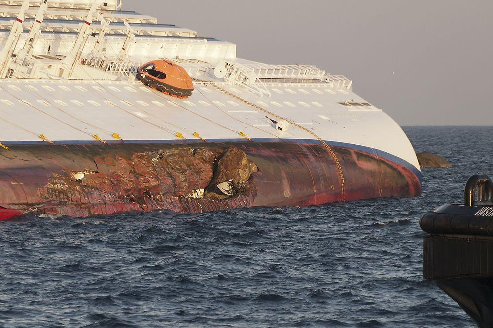 BUNNSKRAPT: En svær stein har boret seg godt fast inn skroget på Costa Concordia under grunnstøtingen. Flengen går gjennom flere vanntette skott. Store mengder vann trengte dermed inn.